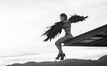 black wings: Black and white photo of beautiful seductive angel woman wearing lingerie and leather belts sitting on the roof edge with wind in her wings over cloudy sky