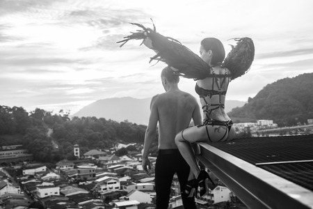 Black and white photo of romantic scene with shirtless man and sensual angel woman wearing lingerie, leather belts and high heels on the rooftop over sky and city landscape background