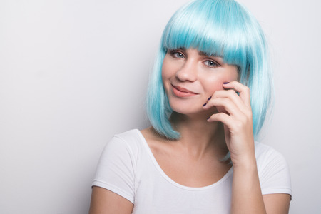 futuristic girl: Cheeky young girl in modern futuristic style with blue wig smiling and looking into the camera over white wall background with copyspace