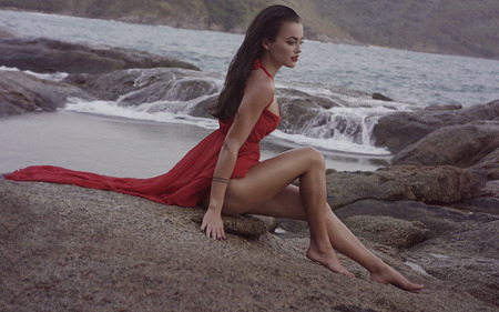 sea sexy: Side view of beautiful sexy glamour woman wearing red dress sitting on the rock by the sea during early cloudy evening. Nature, freedom, beauty, magic, romantic, summer, vacation concept
