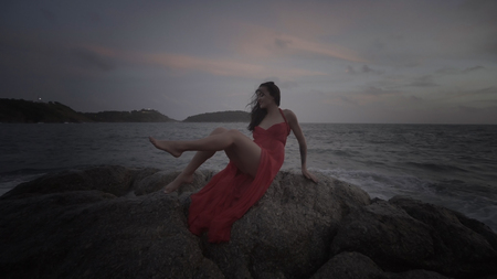 sexy glamour: Beautiful sexy glamour woman wearing red dress smiling while sitting on the rock by the sea during early cloudy evening. Nature, freedom, beauty, magic, romantic, summer, vacation concept