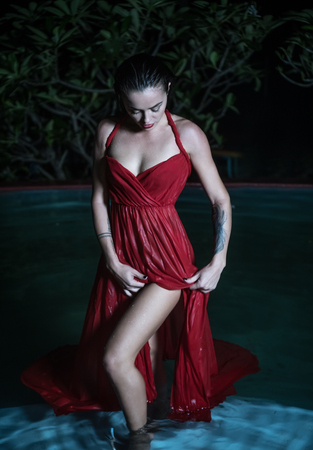 wet dress: Beautiful fashion mysterious woman wearing red elegant wet dress standing in the pool at night Stock Photo