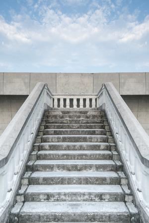 stonemason: Bottom view stairs of white stonemason bridge against the blue cloudy sky during summer day