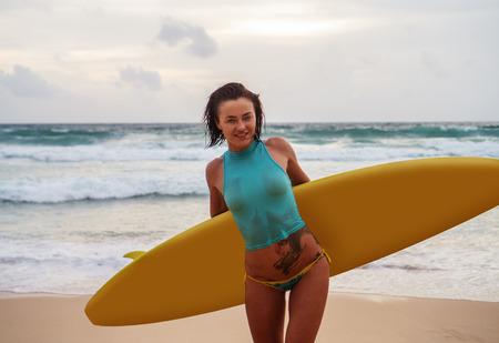 archivio fotografico brunette bella donna che indossa top bagnato e slip sorridente mentre in piedi sulla spiaggia con il surf giallo durante giorno