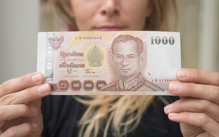 baht: Closeup of 1000 Thai Baht note withdrawned from ATM over blurred womans face