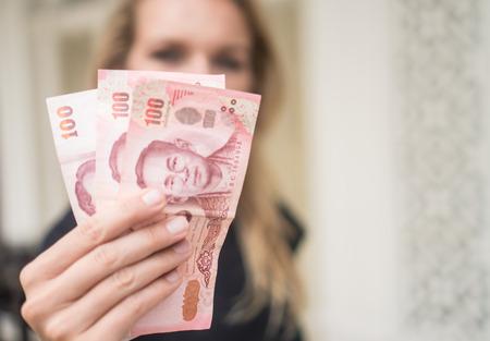 automatic transaction machine: Primer plano de 100 notas del baht tailandés retiradas del cajero automático sobre la cara de la mujer borrosa Foto de archivo