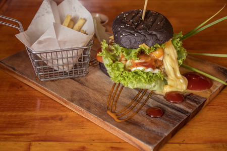 Closeup of beautifully served black burger with French fries isolated on wooden cutting board
