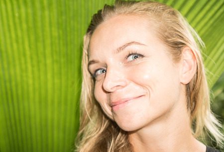 looking into camera: Closeup of happy blond woman looking into camera over green tropical leaf background