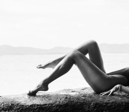 Schwarz-Weiß-Fotografie Nahaufnahme von sexy gebräunte Bikini Körper Frau auf Strandurlaub. Nahaufnahme der Beine und Unterkörper in Badehose von gesunden und fitten schönes Mädchen liegend dwon auf Felsen über Meer Hintergrund