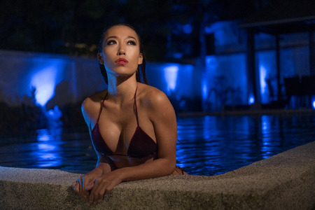 bikini pool: Beautiful sensual Asian woman in sexy bikini with wet hair standing in the water with hands on the edge of swimming pool during summer evening over amazing blue lights background