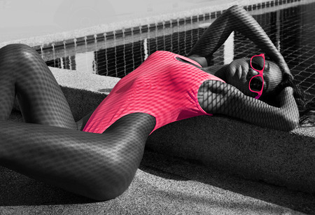 health woman: Beautiful healthy sexy woman with fit body in fashionable elegant pink bikini swimsuit and sunglasses lying down and posing with fishnet shadow pattern on her body beside the swimming pool - black, white and pink photo