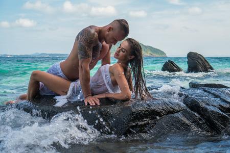 nue plage: Sensuelle jeune couple dans des vêtements blancs portant sur la roche par la mer sur le ciel et l'île tropicale de fond