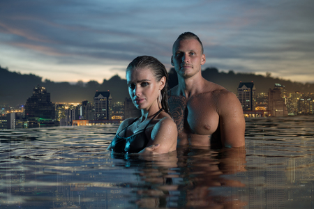 romantic sky: Romantic sensual couple alone in infinity swimming pool over beautiful tropical and sunset sky background