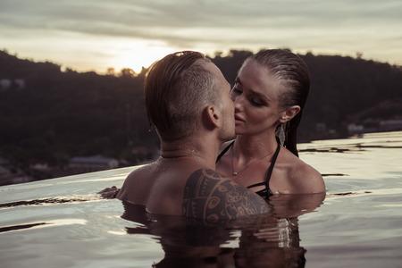 美しい熱帯と夕焼け空を背景にインフィニティ ・ スイミング プールで一人でロマンチックな官能的なカップル