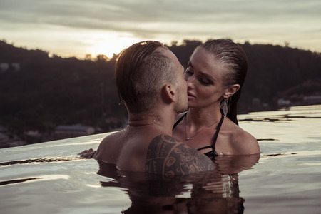 e4ac41682b Romantic sensual couple alone in infinity swimming pool over beautiful  tropical and sunset sky background