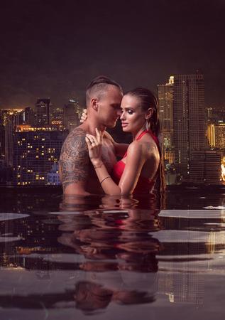 Romantico coppia sensuale soli in piscina a sfioro sopra bella città vista sfondo