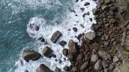 water splashing: Aerial top view of sea waves hitting rocks on the beach in Phuket, Thailand