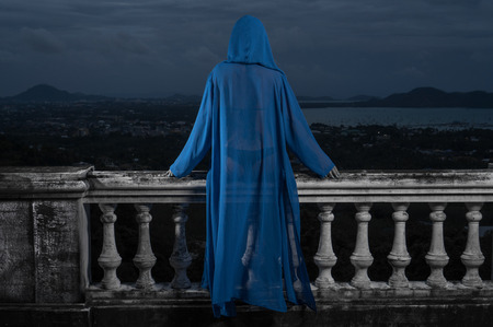 hoody: Back view of mysterious woman in black bikini and blue hoody cover up sitting on old stone ornate carved balustrade over cloudy sky and cityscape