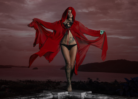 hoody: Mysterious beautiful woman in black crochet bikini and red hoody cover up posing in wind over cloudy sky and cityscape