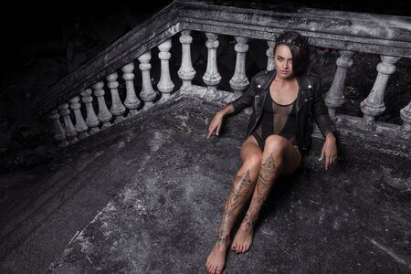 Mysterious beautiful woman in black bodysuit, leather jacket and crown with henna tattoo on her legs sitting leaning against old stone steps with ornate carved balustrade while looking at the camera