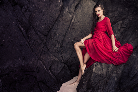 wet dress: Beautiful brunette glamour woman in red dress with wet hair leaning against the rock