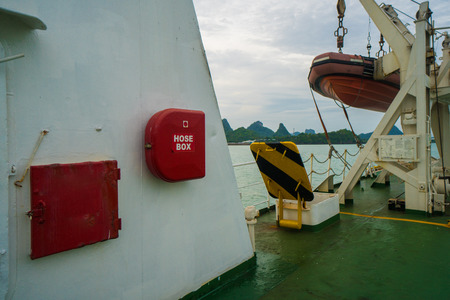 Fire hose cabinet and rescue motor-boat in the ferry ready for action over sea and sky background
