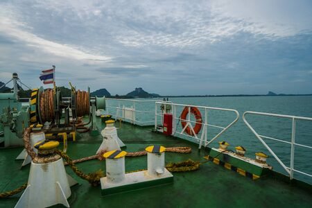 Anchors rope coil and life buoy on bow with Thai flag of touristic cruise boat over sea, sky and mountains background Editorial