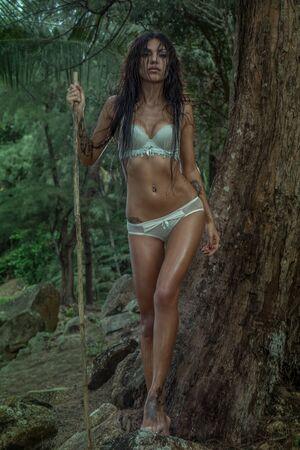 selva: Sensual joven belleza morena llevaba ropa interior de la menta con el pelo mojado, con aspecto de mujer del amazonas, de pie con palo de madera sobre fondo verde selva tropical
