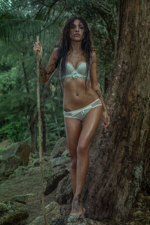 Sensual young brunette beauty wearing mint underwear with wet hair, looking like amazon woman, standing with wooden stick over tropical green jungle background