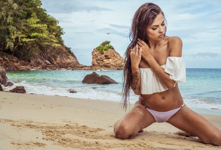 wet bikini: Sensual young brunette beauty wearing white top and bikini bottom with beautiful hair sitting on the beach over beautiful sea, sky and tropical island background Stock Photo