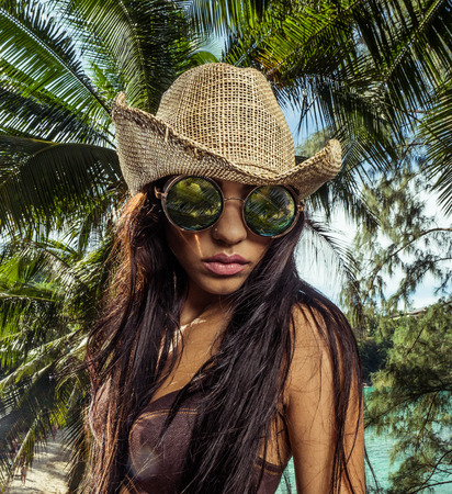 Closeup face of attractive brunette girl with straw hat and sunglasses standing in tropical palm trees forest over beautiful beach and turquoise sea background