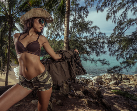 Attractive brunette girl in sexy army look with straw hat and sunglasses standing in tropical palm trees forest over beautiful beach and turquoise sea background