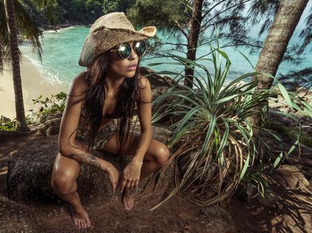 Atractiva chica morena en el ejército sexy mirar con sombrero de paja y gafas de sol sentado en la roca en las palmeras tropicales bosque sobre la hermosa playa y mar azul turquesa