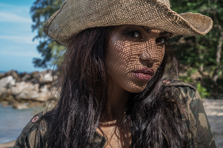 Portrait of beautiful young brunette woman in camouflage jacket and straw hat on a sunny day over tropical island beach background. Face closeup of pretty girl with straw hat pattern shadow on her face Stock Photo