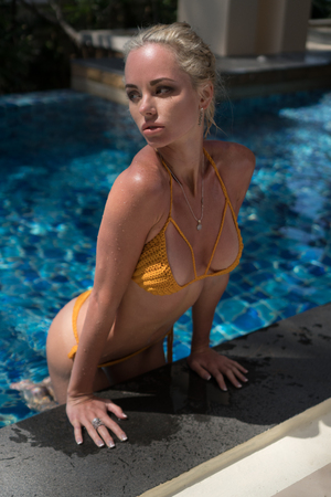 attractive woman: Sensual blond woman wearing crochet bikini relaxing at the edge of swimming pool at tropical resort hotel Stock Photo