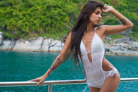 Mujer joven morena en traje de baño blanco que se coloca en el yate en el día soleado de verano, brisa del desarrollo de pelo, mar turquesa y la isla tropical en el fondo Foto de archivo