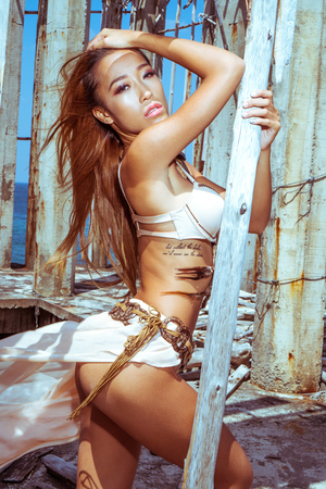 over the sea: Mysterious sensual tribal woman with long hair wearing ethnic outfit and jewellery looking into the camera while posing between concrete and wooden pillars over beautiful blue sea and sky background