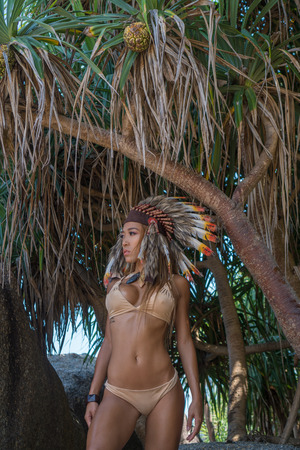 body jewelry: Sensual Native American Indian looking woman wearing nude bikini and indian feather hat looking aside while standing between tropical tress on sunny summer day Stock Photo