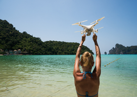 Back view of woman standing on the beach with raised hands holding drone over beautiful sea and summer blue sky background Stock Photo
