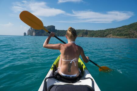 Back view of woman kayaking in turquoise sea during summer day. Travel tropical island holiday concept