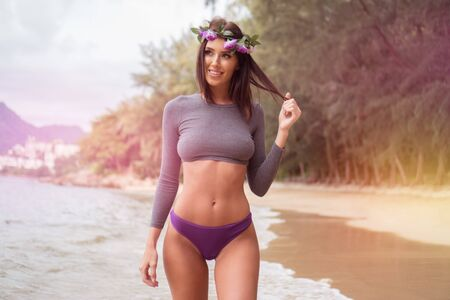 junge nackte mädchen: Sensual brunette woman wearing gray long sleeve top, purple underwear bottom and wreath smiling while walking on the sandy beach over beautiful tropical island background
