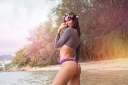 sexy girl nude: Sensual brunette woman wearing gray long sleeve top, purple underwear bottom and wreath looking into the camera and smiling while standing on the sandy beach over beautiful tropical island background
