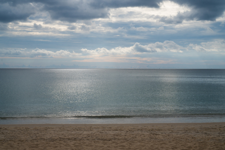 refelction: View from sandy beach on dramatic tropical cloudy sky and sea