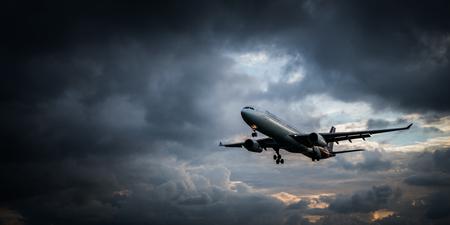 Mening van het strand op het landende vliegtuig dat over mooie bewolkte dramatische kijkende hemelachtergrond wordt geïsoleerd