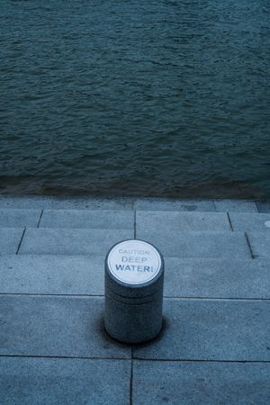 Deep water caution sign over concrete steps and water background Stock Photo
