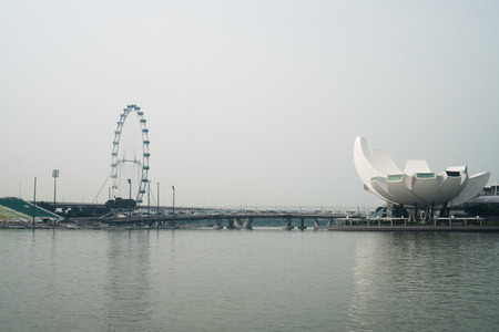 finacial: View of Art Science Museum and Ferris Wheel in Singapore during cloudy day Editorial