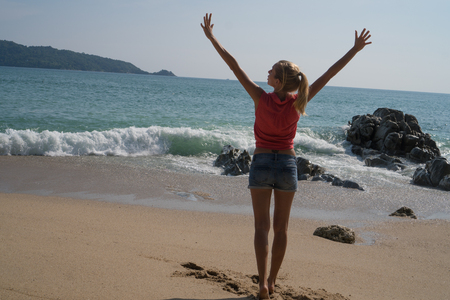 careless: Back view of female tourist in red shirt and blue shorts standing on the beach with raised hands and enjoying summertime over turquoise sea and sky background