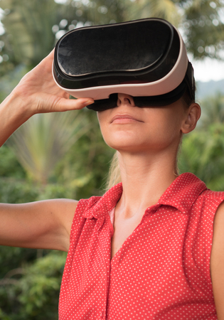 Closeup portrait of woman having fun with virtual reality glasses over green tree background