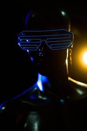 led lighting: Closeup face and torso of female mannequin in blue led glasses over dark background Stock Photo