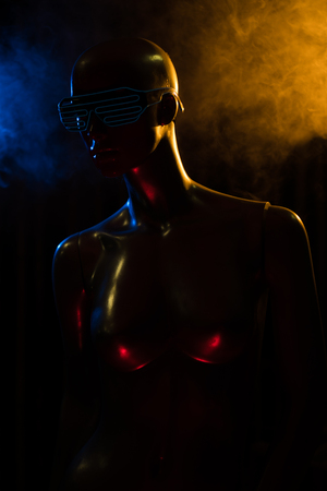 Closeup face and torso of female mannequin in blue led glasses over dark smokey background
